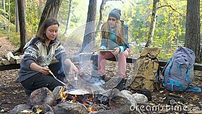 Kvinnliga vänner lagar traditionella pannkakor över en öppen brand i lägret utomhus under en hike arkivfilmer