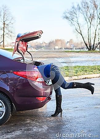 Kvinnligt lägger benen på ryggen från bilstammen