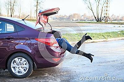 Kvinnligt lägger benen på ryggen att svänga henne in i bilbagagestammen
