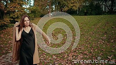 Kvinnor går genom höstparken, det är kallt att lägga bruna rock på kroppen för att hålla varm stock video