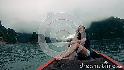 Kvinnor sitter i en båt på en flod under regn arkivfilmer