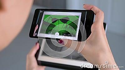 Kvinnor som använder smarta telefoner och surfplatta med AR-program - samtida konst arkivfilmer