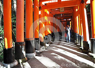 KYOTO, JAPAN - OCT 23 2012: A man takes photos of torii gates at Editorial Stock Photo