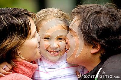 Kyssande föräldrar för dotter