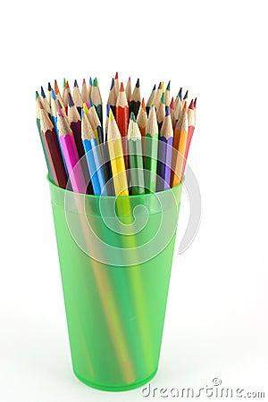 Lápices del color en el apoyo verde
