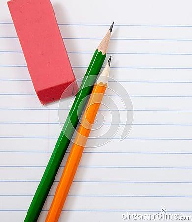Lápices y un borrador en el papel del cuaderno