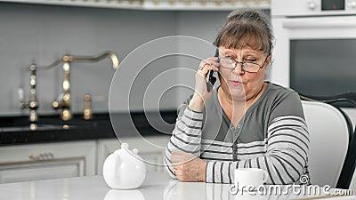 Lächelnde attraktive Senior Lady genießt die Kommunikation auf dem Handy beim Tee trinken stock video footage