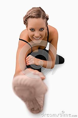 Lächelnde Frau, die Ausdehnungen auf dem Fußboden tut