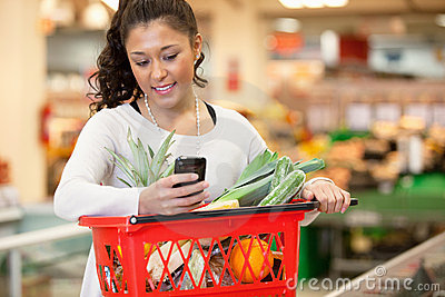 Lächelnde Frau, die Handy im Einkaufenspeicher verwendet