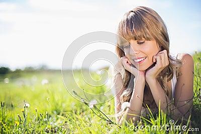 Lächelnde junge Frau auf dem Gras, das Blumen betrachtet