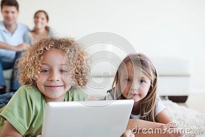 Lächelnde Kinder, die einen Tablettecomputer verwenden
