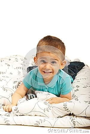 Lächelnder Junge, der auf Decke liegt