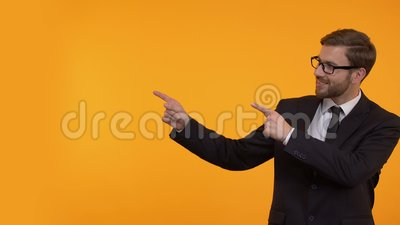 Lächelnder Mann in der Klage zeigend auf gelben Hintergrund, Platz für Ihren Text, Schablone stock video
