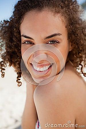 Lächelnder schöner Brunette, der entlang der Kamera anstarrt
