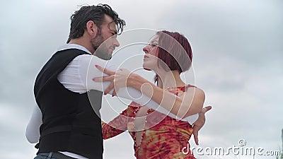 Långsam rörelse av ett par tango-dansare som dansar mot ett molnigt himmel arkivfilmer