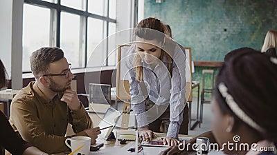 Líder de equipo de sexo femenino que coloca la tabla cercana y que da la dirección al equipo creativo joven Reunión de reflexión  almacen de video