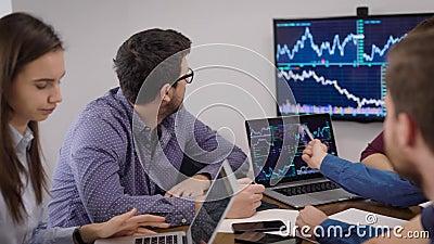 L'équipe de gestion supérieure consulte les schémas et les calendriers de vente sur l'affichage des ordinateurs dans la salle de  banque de vidéos