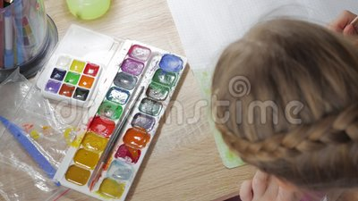 L'adolescente a casa è impegnato nella creatività, disegna l'acquerello ad una tavola nella sala Bambino che disegna vista superi stock footage