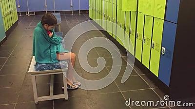 L'adolescente De Fille Dans Le Vestiaire S'essuie Avec Une Serviette Les Cabines Pour Changer Vêtx Après Le Mouvement Lent De Pis Clips Vidéos - Vidéo du syst, sport: 99684025
