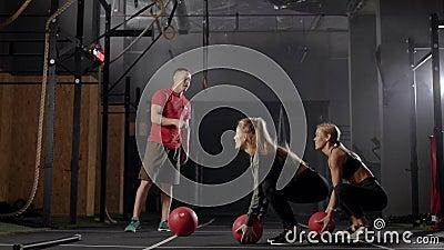 L'allenatore e' in palestra Un uomo fa esercizi a due giovani donne Le bionde imparano la giusta tecnica di esercizio archivi video