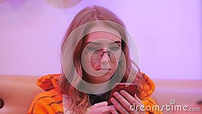 L'animateur de jeune fille habillé comme tigre se reposant dans un café utilise un smartphone banque de vidéos