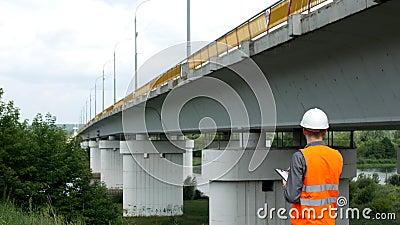 L'architecte vérifie l'état du pont à travers la rivière, enregistre les désavantages, l'examinateur et l'inspecteur clips vidéos