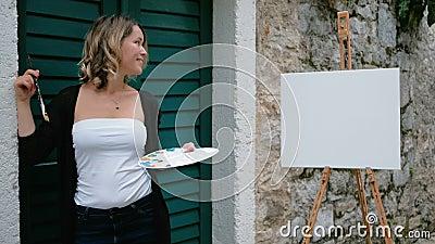 L'artista della donna che si siede sui punti della via e assorbe il cuscinetto della pittura video d archivio