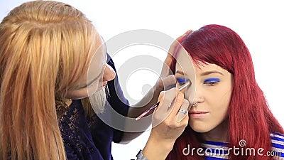 L'artiste de maquillage professionnel teint les yeux du mod?le le styliste peint des cils