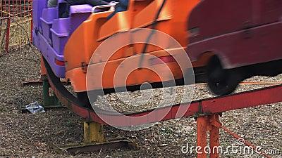 L'attraction colorée du plan rapproché A monte des personnes sur les rails en parc d'attractions au printemps Une attraction d'ar clips vidéos