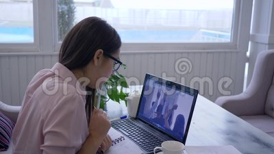 L'e-learning, insegnamento online dei giovani passaggi dagli occhiali femminili per l'autosviluppo utilizza il computer portatile stock footage