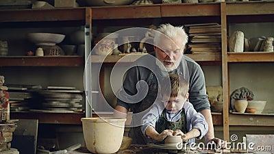 L'enfant concentré forme le pot de l'argile sur la roue du ` s de potier sous des conseils de son grand-père expérimenté ceramic banque de vidéos