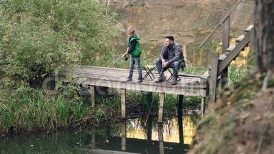 L'enfant mignon de fils du ` s de pêcheur pêche avec son père du pilier en bois tenant la tige tandis que le parent fier regarde  banque de vidéos