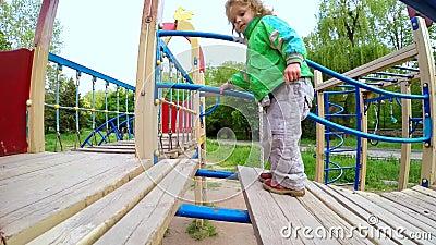 L'enfant se déplace d'une manière ordonnée au-dessus du pont sur le terrain de jeu Mouvement lent banque de vidéos