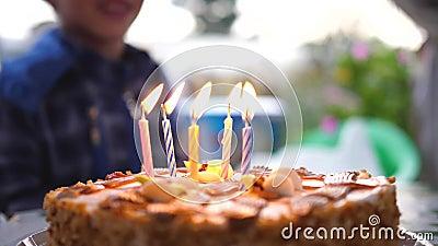 L'enfant se tient en arrière-plan le gâteau pour son anniversaire. Vacances pour enfants banque de vidéos