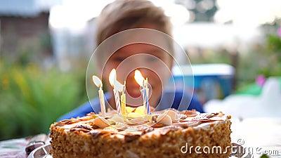 L'enfant souffle les bougies sur le gâteau le jour de son anniversaire Vacances pour enfants banque de vidéos