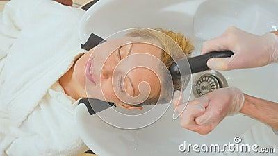 L'estetista dell'uomo lava i capelli del cliente nella clinica di bellezza video d archivio
