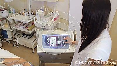 L'estetista lavora all'apparecchiatura di biostimulation che rende alla ragazza un massaggio archivi video