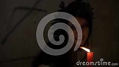 L'exorcisme de la sorcière avec le ricanement mauvais possédé par un démon s'est habillé le grondement noir et en tenant une boug banque de vidéos