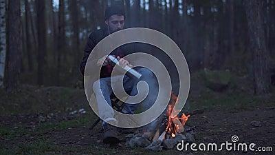 L'homme barbu s'asseyent dans la forêt près du feu et ont mis la boisson dans une tasse de thermos Type non rasé brutal se reposa clips vidéos
