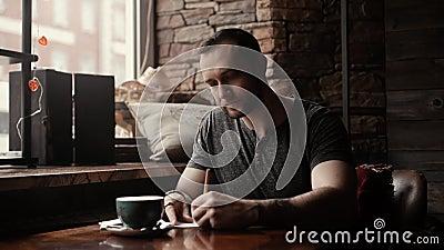 L'homme brutal s'assied en café à la table avec une tasse et fait des entrées dans un journal intime banque de vidéos