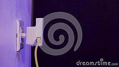 L'homme débranche le câble d'Ethernet du dispositif de supplément de WiFi qui est dans la prise électrique sur le mur banque de vidéos