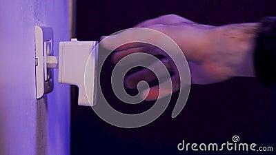L'homme débranche le répétiteur de WiFi de la prise électrique sur le mur banque de vidéos