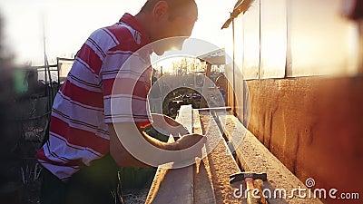 L'homme est métier fonctionnant à un banc de travail avec des machines-outils dans au ralenti pendant le coucher du soleil avec l clips vidéos