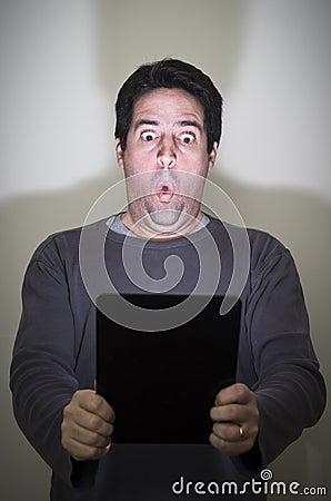 L homme est stupéfié par une tablette digitale