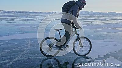 L'homme fait du vélo sur la glace Le cycliste est habillé d'une veste grise, d'un sac à dos et d'un casque Glace congelée clips vidéos