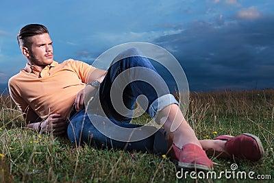 Un gars (vive le titre) L-homme-occasionnel-s-%C3%A9tendant-avec-des-pieds-crois%C3%A9-dans-l-herbe-33659117