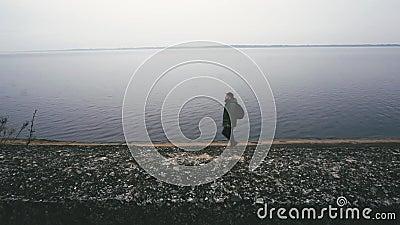 L'homme songeur et concentr? marche le long de la mer Il regarde en avant et in camera, temps de chute et coucher du soleil froid banque de vidéos
