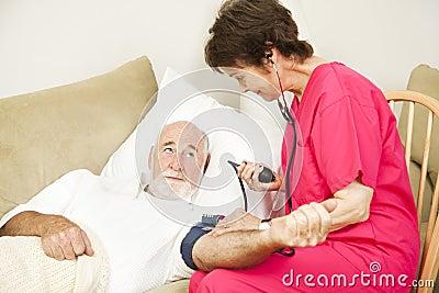 L infirmière de santé à la maison prend la tension artérielle
