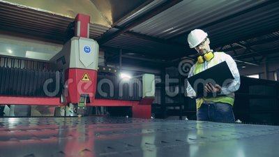 L'ispettore di fabbrica sta osservando l'apparecchiatura laser che taglia metallo video d archivio