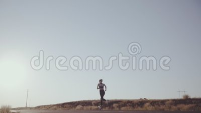 l?ngsam r?relse Flickan på en afton joggar på vägen i sportlikformig stock video